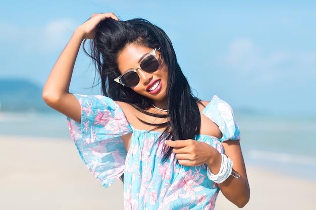 熱帯のビーチで楽しんでいるサングラスとアジアのタイの女の子の肖像画