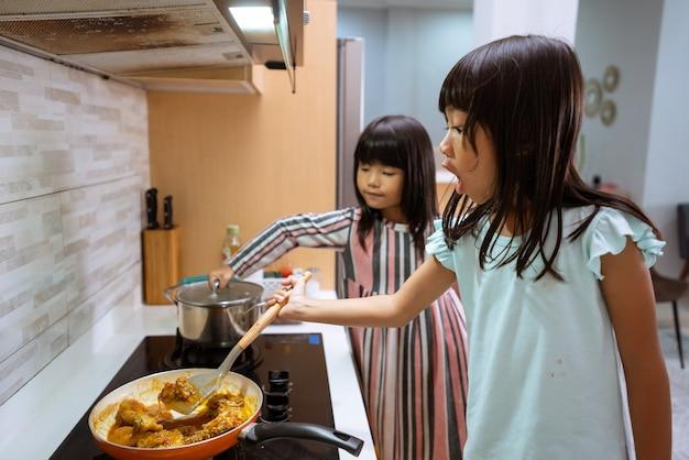 부엌에서 요리 아시아 두 어린 소녀의 초상화