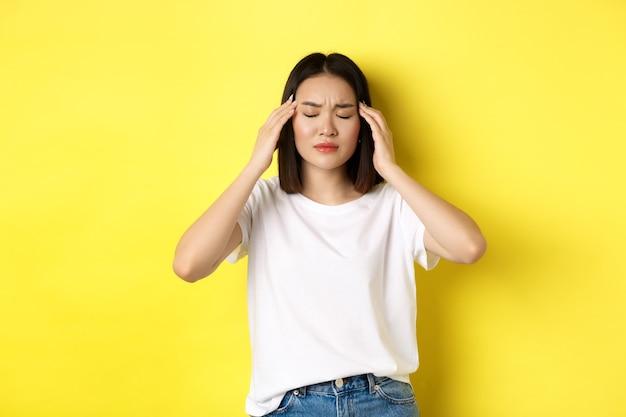 Портрет азиатской женщины закрывает глаза и хмурится от мигрени, касаясь головы, чувствуя головокружение от головной боли, стоя над желтым.