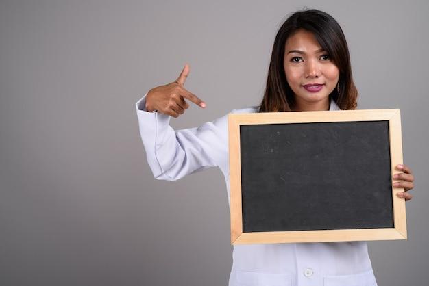 Портрет азиатской женщины-врача, держащей доску