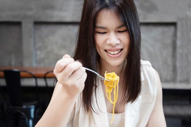 フォークでカボナーラスパゲッティを食べるアジアの女性の肖像画