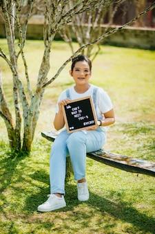 Портрет азиатской женщины, держащей доску с улыбающимся выражением лица в парке