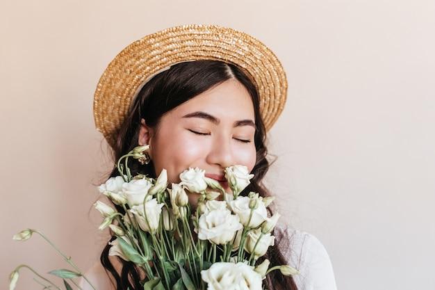 目を閉じて花を嗅ぐ麦わら帽子のアジアの女性の肖像画。白いトルコギキョウの花束を持っている美しい日本人女性のスタジオショット。