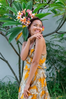 노란색 여름 드레스에 아시아 여자의 초상화는 머리에 plumeria 타이어 꽃과 빛을 가진 둥근 earings 여성 벽과 녹색 숲의 배경에 외부 메이크업 스탠드