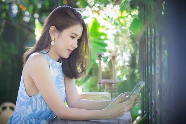 アジアの女性の肖像画長い茶色の髪はスマートフォンを保持します