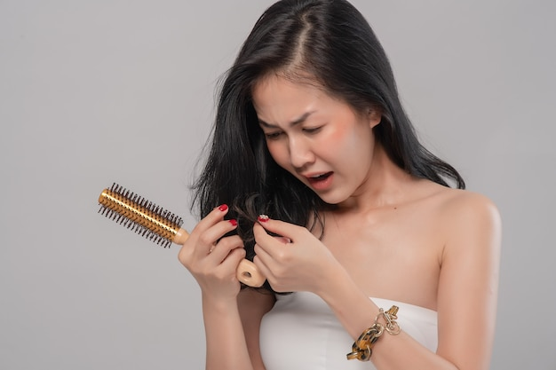 Портрет азиатской женщины с длинными волосами с расческой и проблемными волосами на сером