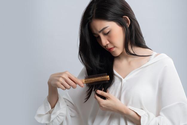 Портрет азиатской женщины длинные волосы с расческой и проблемными волосами на белом.