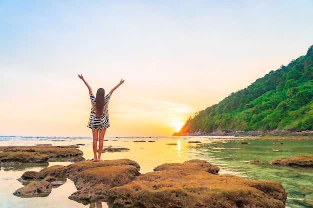 休暇中の海の周りの日没で腕を開いて岩の上のアジアの女性の肖像画