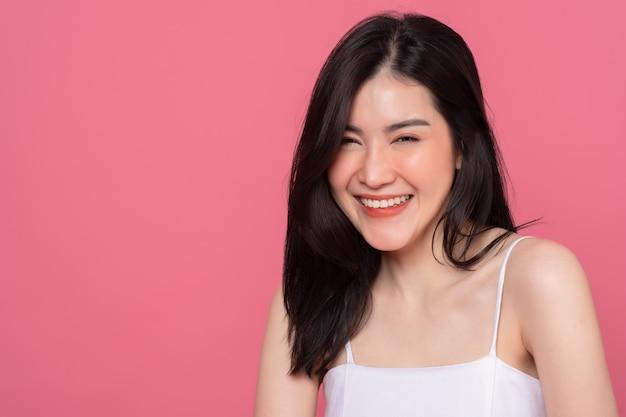 Портрет азиатской женщины позирует, чувствуя себя очень счастливой, пораженной, взволнованной и удивленной над розовым