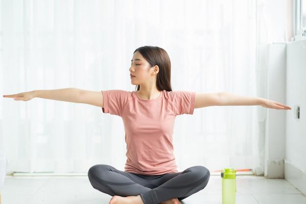 Портрет азиатской женщины, практикующей йогу дома