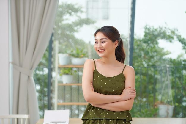 リビングルームで腕を組んで立っているアジアの女性の肖像画