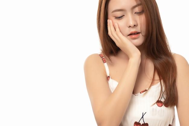 Портрет азиатской женщины страдая от боли зубной боли на белой предпосылке, женщины с зубной болью; концепция стоматологической помощи; закройте вверх по азиатской модели женщины.