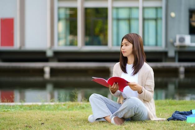 Портрет азиатской студентки университета женщины, сидящей на траве в кампусе, выглядящей счастливой и читающей книгу в парке.