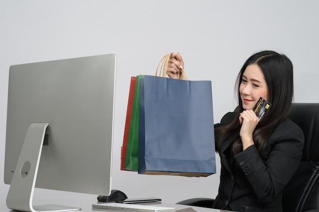 スマートフォンとコンピューターを使用し、自宅でオンラインショッピングのためのクレジットカードとショッピングバッグを保持しているアジアの女性の肖像画。オンラインショッピングの概念