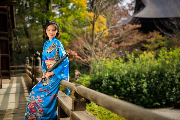 Портрет азиатской женщины нося японское голубое кимоно и зонтик на держать руку в парке