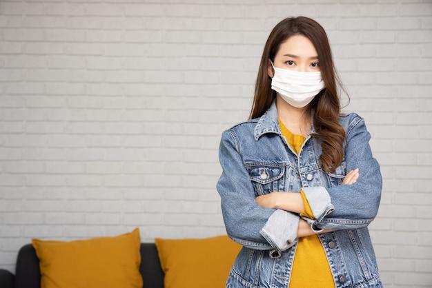 바이러스 코비드-19를 방지하기 위해 보호용 의료 마스크를 쓰고 집 거실에서 팔짱을 낀 아시아 여성의 초상화