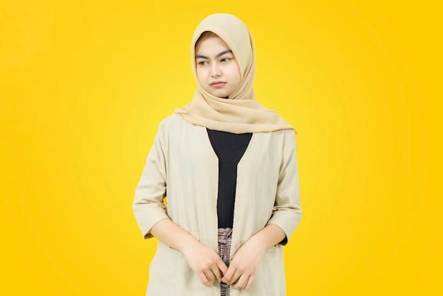 黄色の壁に悲しそうな顔を持つアジアの女性の肖像画