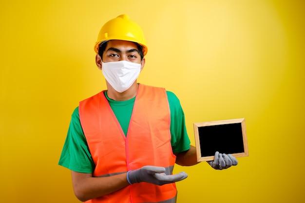 노란색 배경에 작은 칠판을 들고 코로나바이러스에 대한 보호 마스크를 쓴 아시아 노동자의 초상화