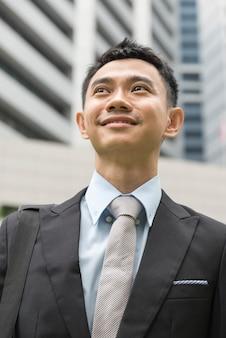 ブリーフケースを手に持って都市に分離されたアジアの若いビジネスマンの肖像画