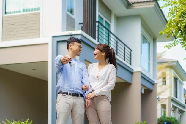 Портрет азиатской молодой пары, стоящей и обнимающейся вместе и держащей ключ от дома, счастливой перед своим новым домом, чтобы начать новую жизнь. семья, возраст, дом, недвижимость и люди концепции.