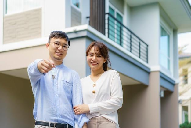 Портрет азиатской молодой пары, стоящей и обнимающейся вместе и держащей ключ от дома, выглядящей счастливой