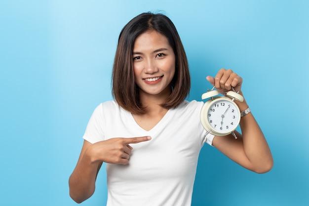 目覚まし時計を保持しているアジアの若い女の子の肖像画