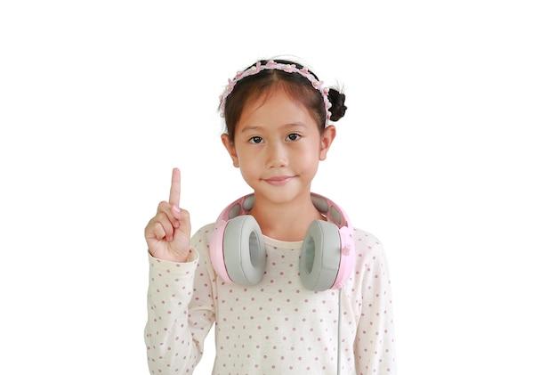 Портрет азиатского ребенк маленькой девочки с наушниками на шее показывает один указательный палец изолированный на белой предпосылке.