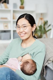 彼女の生まれたばかりの女の子を母乳で育てている間カメラに微笑んでいる眼鏡のアジアの若い母親の肖像画...