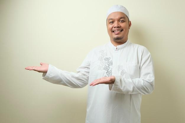 상아 배경 복사 공간과 함께 웃으면서 자신의 옆에 뭔가를 제시하는 가리키는 아시아 젊은 이슬람 남자의 초상화