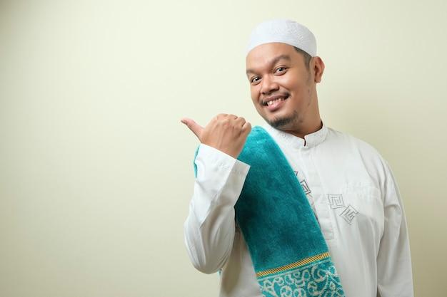 웃으면서 옆에 뭔가를 제시하는 아시아 젊은 이슬람 남자의 초상화