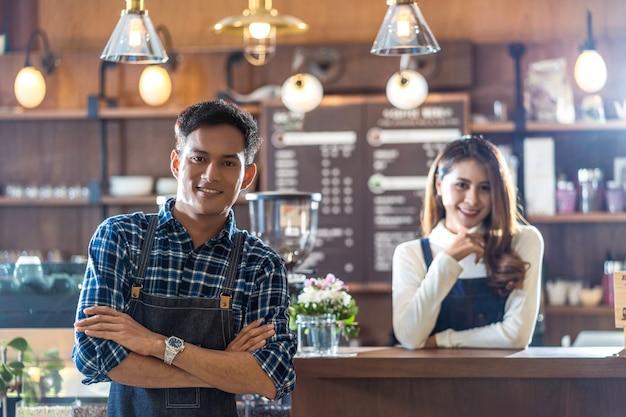 Портрет азиатского молодого владельца малого бизнеса с кафе перед барной стойкой