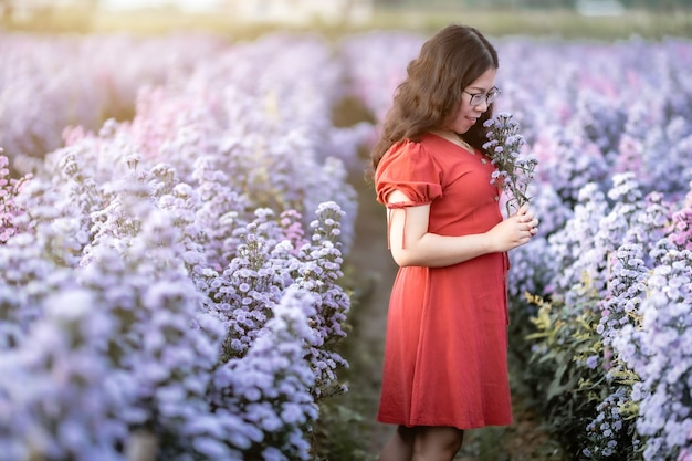 Портрет азиатской молодой женщины счастливый путешественник с красным платьем, наслаждаясь в белом цветущем или фиолетовом цветочном поле маргаритки майклмас в саду природы в чиангмае, таиланд, путешествие расслабиться в отпуске
