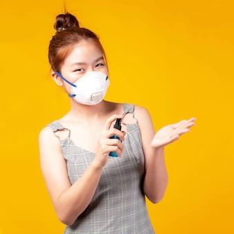 黄色の背景に分離されたコロナウイルスcovid-19を保護するために手を洗うためにアルコールを保持しているフェイスマスクを身に着けているアジアの若い女性の肖像画、広がりcovid19を保護するために自分自身を隔離します。