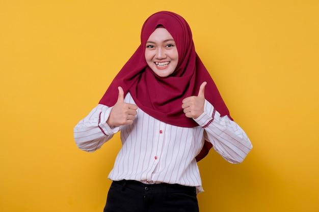 Hijab를 입고 아시아 젊은 여자의 초상화는 두 엄지 손가락을주고 행복하게 표정을 바라본다.