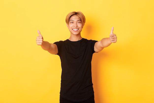 黄色の壁に立っている、アイデアのような承認で親指を示す保証されたハンサムなアジア人の肖像画