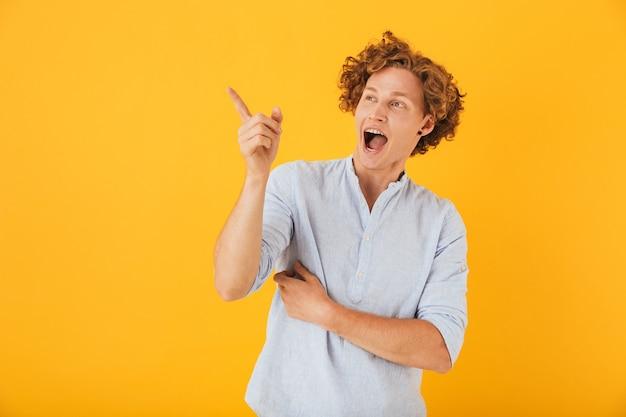 Портрет изумленного кудрявого мужчины, показывающего пальцем и с удивлением смотрящего на copyspace, изолированный на желтом фоне
