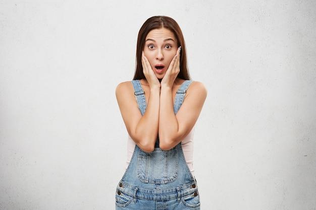 Портрет удивленной эмоциональной брюнетки в стильном джинсовом комбинезоне, открывающей рот и держащей лицо обеими руками, потрясенной неожиданными новостями, ее взглядом и жестами, выражающими удивление