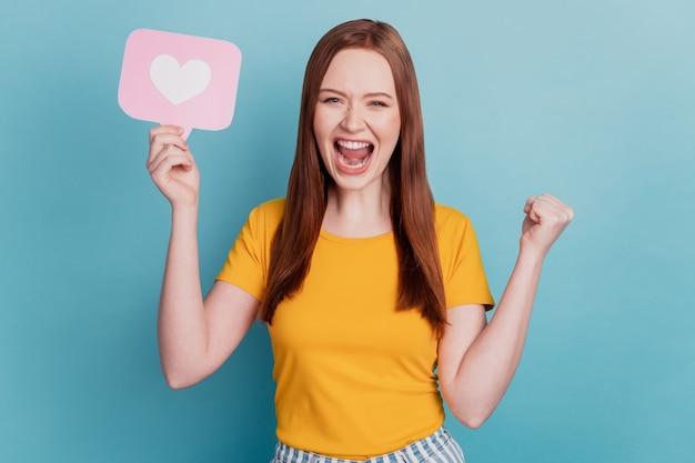 놀란 흥분된 여성의 초상화는 파란색 배경에 심장 아이콘 카드를 들고 주먹 비명을 지른다