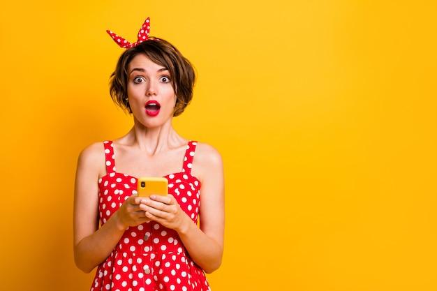 Портрет удивленной смешной сумасшедшей девушки использует мобильный телефон, читает невероятную информацию в социальных сетях, впечатлен крик, вау, омг, носить одежду в стиле ретро, изолированную над блестящей цветной стеной