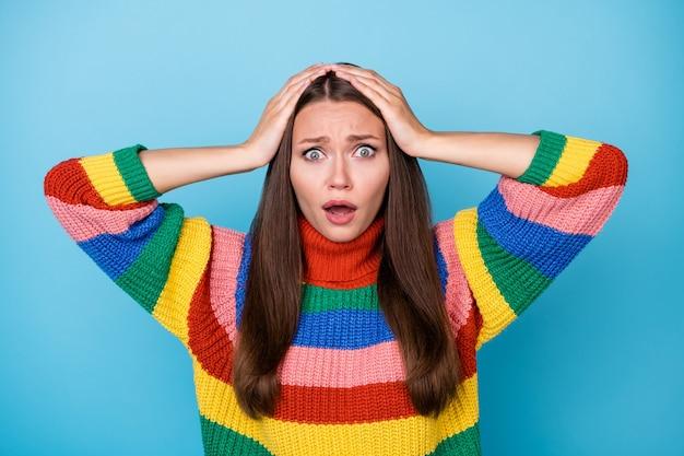 놀란 소녀의 초상화는 끔찍한 lgbt 뉴스 터치 손 머리에 파란색 배경 위에 고립 된 세련된 유행 무지개 점퍼를 입고 두려움 좌절감을 느낀다