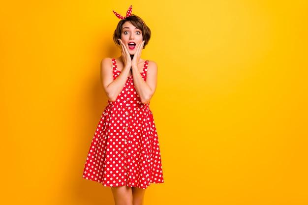 Портрет удивленной девушки слышит невероятную неожиданную новизну впечатлен прикосновением рук лицо крик носить юбку в горошек, изолированную над яркой цветной стеной