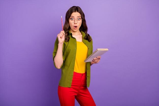 놀란 소녀의 초상화는 카피북 메모 보고서에 깊은 인상을 받았습니다. 빨간 바지 바지 스타일의 세련된 고립된 보라색 배경에서 연필을 들어올리는 놀라운 아이디어가 있습니다
