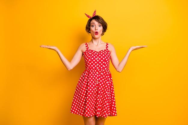 Портрет удивленной девушки, держащей руку, демонстрирует невероятную рекламу, продвижение впечатлен крик, вау, боже мой выбор, выбор, решение, носить юбку в горошек, изолированную над яркой цветной стеной