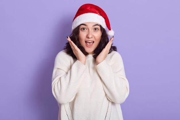 ライラックの壁に隔離されたサンタクラウスの帽子と暖かい白いセーターの驚いた女の子の肖像画