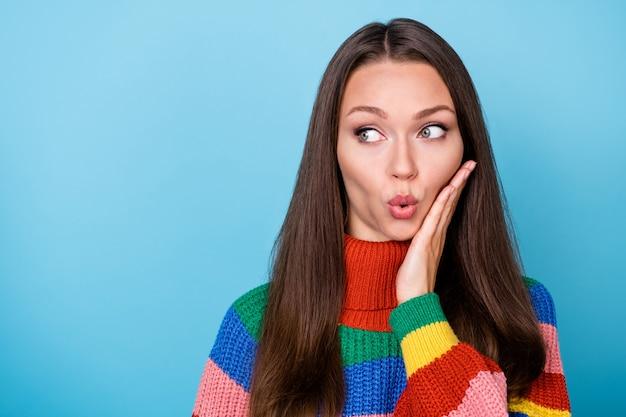 놀란 소녀 모양 카피스페이스의 초상화는 푸른 색 배경 위에 격리된 무지개 스웨터를 입고 소문 가십 비밀 터치 손 얼굴에 감동