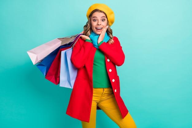 驚いた女の子のショッピングセンターのクライアントの肖像画は、ターコイズ色の背景の上に分離された赤青緑黄色の帽子を着用します。