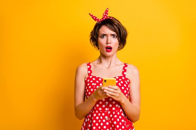 Портрет удивленной девушки, использующей смартфон, прочитайте информацию в социальных сетях, впечатлен крик, вау, боже, невероятно неожиданная одежда, красивая одежда, изолированная над яркой цветной стеной