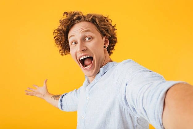 黄色の背景で隔離、自分撮り写真を撮って叫んで驚いた幸せな男の肖像画