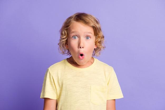 Портрет удивленного маленького мальчика смотрит в камеру с открытым ртом, изолированным на фиолетовом фоне