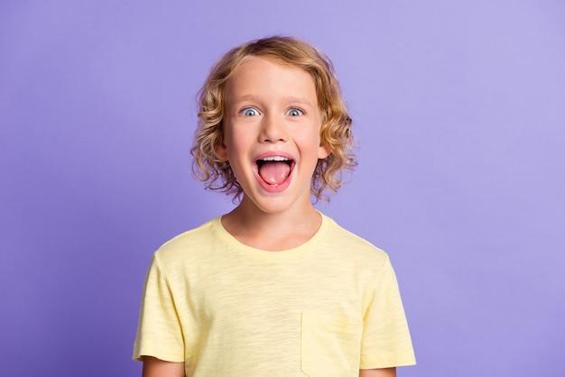 Портрет удивленного маленького мальчика смотрит в камеру, громко кричит, носит желтую одежду, изолированную на фиолетовом цветном фоне